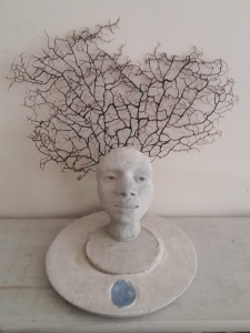 """Animist Head with Coral"" installation with cement head and coral"