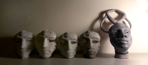 Shot of mask and head sculptures in progress in an artist's studio