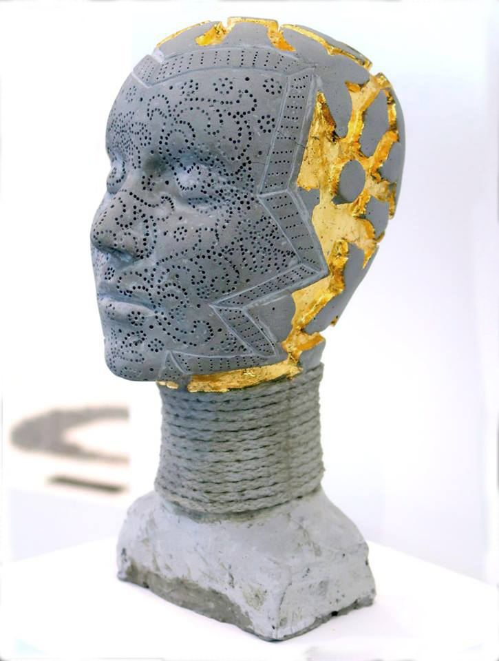 """""""In This Skin"""" cast cement head with gold leaf"""